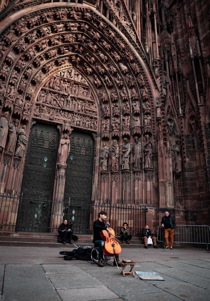 homme violoncelle devant cathédrale